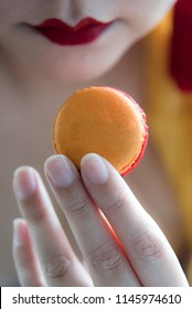Beautiful fingers of Asian woman hold a colorful and delicious orange color macaron during afternoon tea or high tea against herself wearing red lips. Elegant oriental setting. Natural lighting.