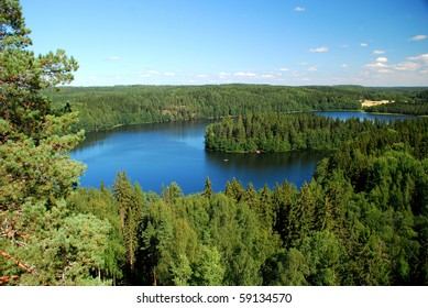 A beautiful Finish landscape taken in the region of a thousand lakes, in Finland. We can see lakes and forests with firs, and a sunny blue sky.