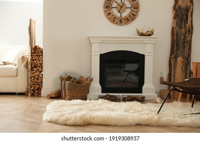 Beautiful fireplace and basket with firewood in contemporary room interior
