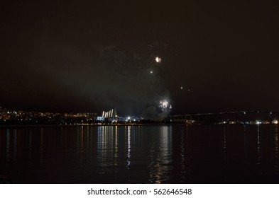 Beautiful firework on night sky in tromsoe city with bridge, cathedral and colorful reflection on the cold fjord water surface. Delayed new years eve firework due to weather, launched in january 2017