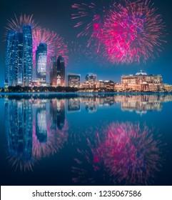 Beautiful fireworks above Abu Dhabi Skyline at night with reflection on water, United Arab Emirates