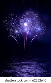 Beautiful fireworks in the night sky with reflection on water