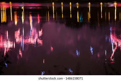 Beautiful fireworks over the city with reflection in the water, closeup and bokeh, blur effect, purple