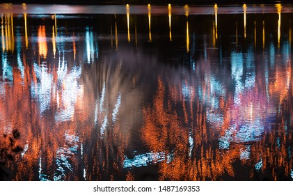 Beautiful fireworks over the city with reflection in the water, closeup and bokeh, blur effect, yellow