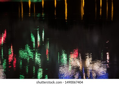 Beautiful fireworks over the city with reflection in the water, closeup and bokeh, blur effect, green