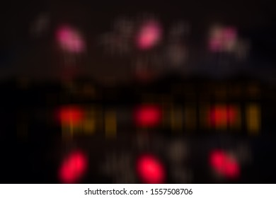 Beautiful fireworks over the city with reflection in the water with blur effect