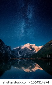 Beautiful first light on a mountain top against stars and milky way in Lago Di Praies, Dolomites, Italy. Two image composite.
