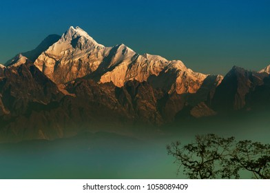 Beautiful first light from sunrise on Mount Kanchenjungha, Himalayan mountain range, Sikkim, India. Orange tint on the mountains at dawn.