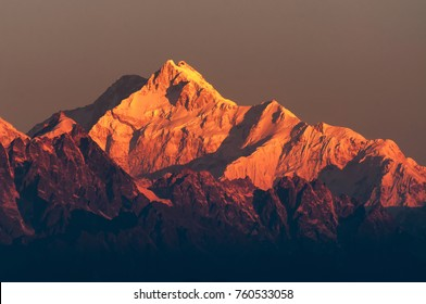 Beautiful first light from sunrise on Mount Kanchenjugha, Himalayan mountain range, Sikkim, India. Orange tint on the mountains at dawn.