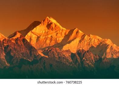 Beautiful first light from sunrise on Mount Kanchenjugha, Himalayan mountain range, Sikkim, India. Orange tint on the mountains at dawn.