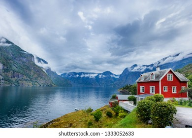 Beautiful fishing red house on fjord. Beautiful nature with blue sky, reflection in water, rocky beach and fishing house. Norway