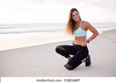Beautiful fit and attractive young adult woman kneels down on the beach looks to her left with a big beaming happy smile. The model is flexing her abs and is so pleased to be fit and healthy.