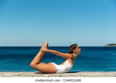 Beautiful fit attractive young woman wearing white swimsuit working out outdoors on summer day, doing basic posture Dhanurasana, Bow Pose, full length