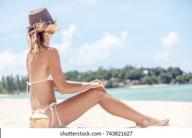 Beautiful fit body girl on travel vacation. Sexy bikini body woman playful on paradise tropical beach