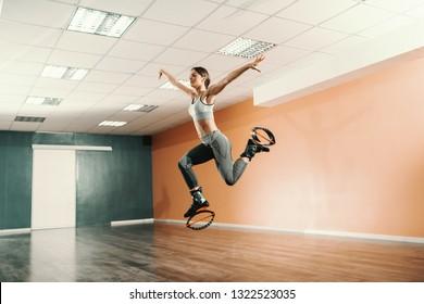 Beautiful fit Caucasian brunette in sportswear jumping on kangoo jumps footwear in gym.