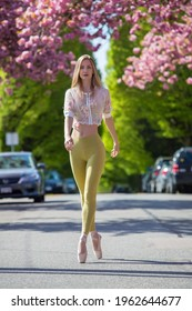 A beautiful fit Caucasian woman walking in the street on the pointy shoes in a blurry cherry blossom on the background, spring, sunny day