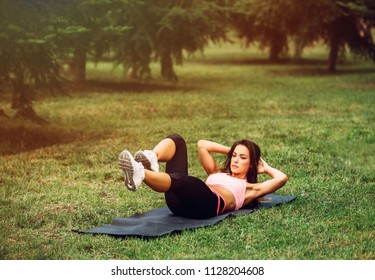 Beautiful fit girl doing crunches outside in park