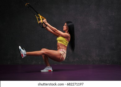 Beautiful fit girl exercise in gym with trx.