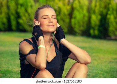 Beautiful fit girl relaxing after good workout, enjoying sun lights with closed eyes, tanning and listening music, meditation outdoors, harmony and soul balance concept