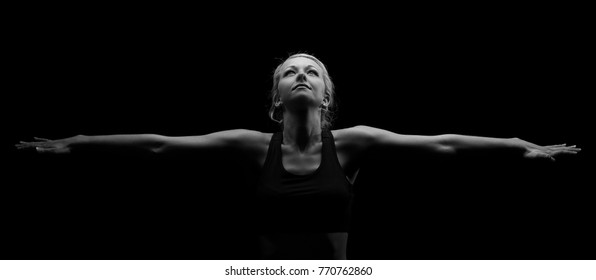Beautiful fit and healthy blond woman in black top in the dark with arms stretched artistic conversion