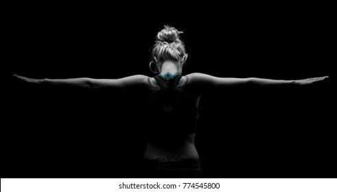 Beautiful fit and healthy blond woman in black top in the dark with arms stretched from behind artistic conversion