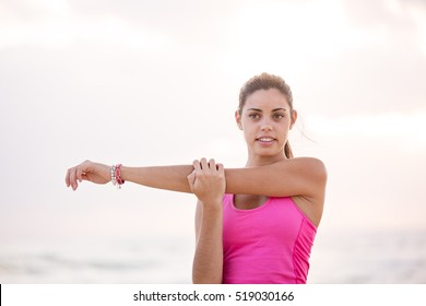 Beautiful fit and healthy woman stretches her arm across her chest preparing for a exercise workout.