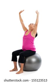 Beautiful fit Hispanic pregnant woman sitting on an exercise ball stretching with arms extended isolated on a white background