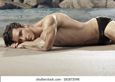 Beautiful fit man laying on exotic beach