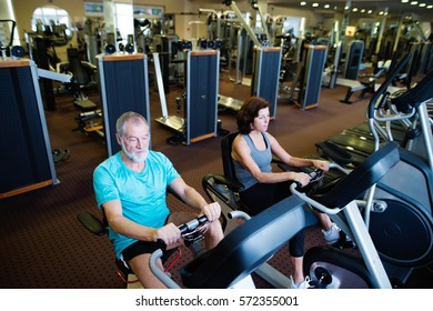 Beautiful fit senior couple in gym doing cardio work out.
