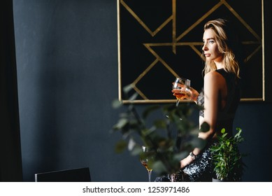 Beautiful fit slim blond woman with seductive make up in black sexy lingerie in loft home rich interior.  Gorgeous woman with a glass of wine