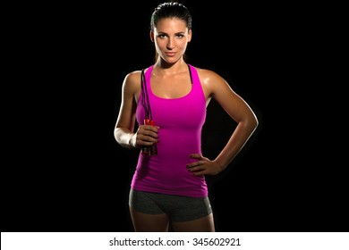 Beautiful fit thin slim toned female body jump rope athlete isolated on black standing confidently