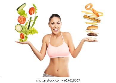 Beautiful, fit woman choosing between a healthy and unhealthy food