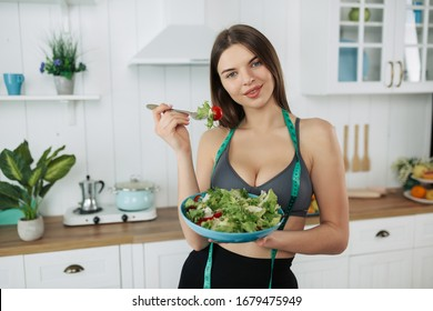 Beautiful fit woman eating healthy salad after fitness workout.