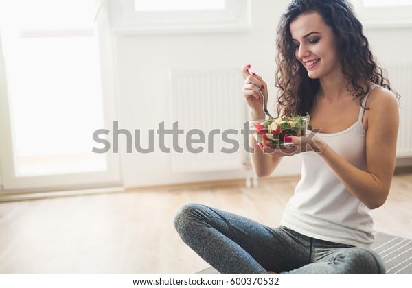 フィットネストレーニングの後、健康的なサラダを食べる美しいフィット女性