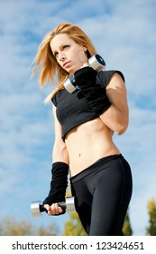 Beautiful fit woman exercising  outdoors over a sky background