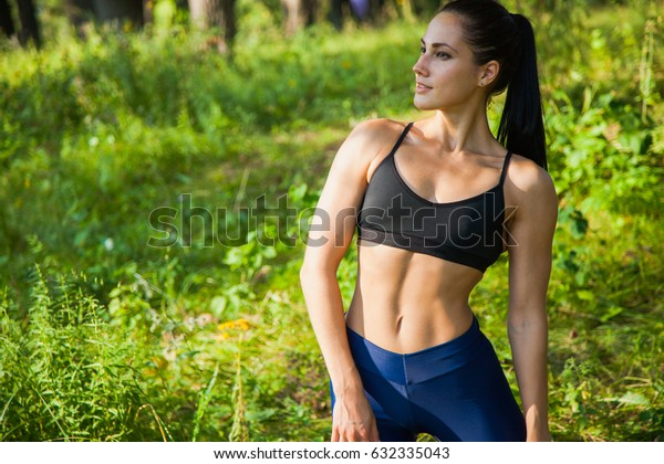 Beautiful fit woman fitness exercises outdoors. Go in for sports in nature forest and green grass
