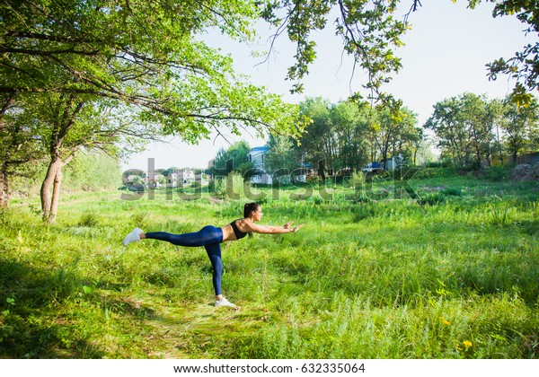 Beautiful fit woman fitness exercises outdoors. Go in for sports in nature forest and green grass. Stretching muscles. Yoga outside