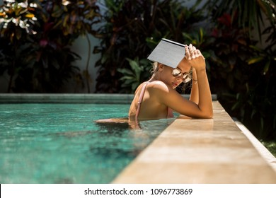 Beautiful fit woman in sexy bikini and sunglasses in a pool spa hotel make shadow with a note book. Relax vacation concept. Hot summer idyllic day, student girl, smart hipster lifestyle advertising.