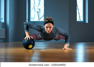 beautiful fit woman in sportswear posing while sitting on the floor with basketball in front of window at gym Healthy girl lifestyle and sport concept
