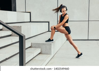 Beautiful and fit woman stretching. Caucasian woman working out on steps outdoors.