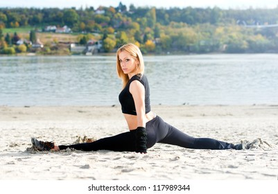 Beautiful fit woman stretching on the beach