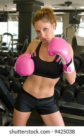 Beautiful, fit woman wearing hot pink boxing gloves.