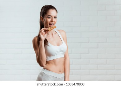 Beautiful, fit young woman eating a healthy whole grain bar