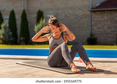 Schöne junge Frau, die im Freien am Pool trainiert, um Sitzaufnahmen zu machen