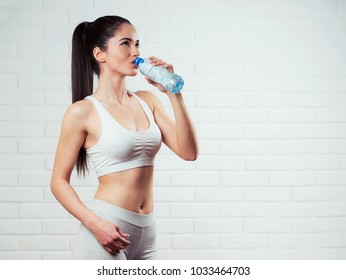 Beautiful, fit, young woman holding a bottle of water