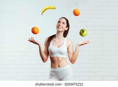 Beautiful, fit, young woman joggling with fruit, over a white brick wall