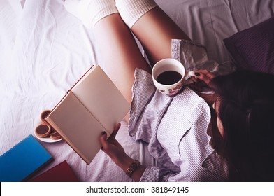 Beautiful fit young woman reading morning book in her bed and drinking coffee from large cup