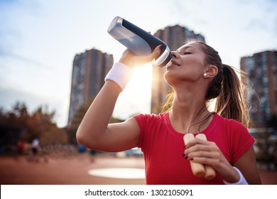 Beautiful fitness athlete woman drinking water after workout in city.