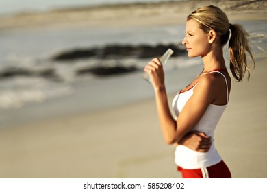 Beautiful fitness athlete woman drinking water after work out exercising on sunset evening summer in beach