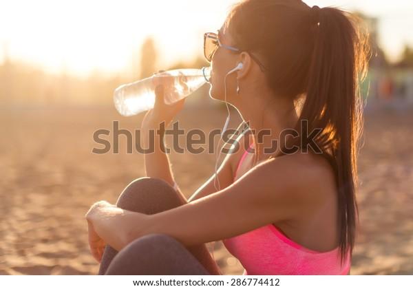 夕暮れの夏の夕方の運動の後、海浜のアウトドアポートレートで水を飲む美しいフィットネス選手の女性